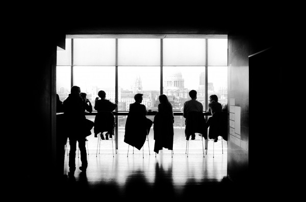 black-and-white-image-of-people-sitting-in-conference-room